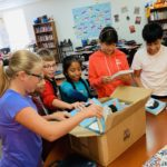 students pulling new books out of a box