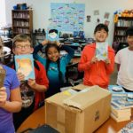 students showing off their new books