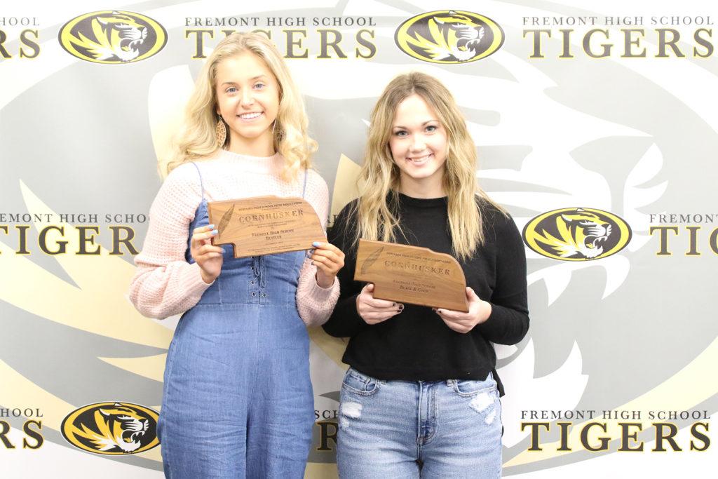 two girls holding journalism awards